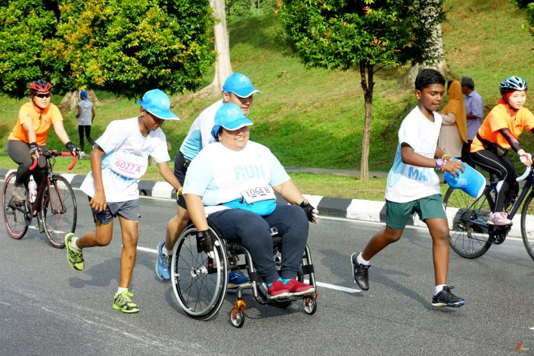 Kiren Paranasivam, 14 y.o. mentee together with Care2Run volunteer, Joe Liew, voluntarily giving the wheelchair bound runner, Yuhanis Adnan, a push